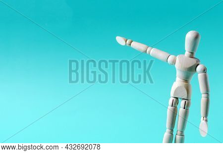 The Figure Of A Wooden Man With An Outstretched Arm On A Blue Background. The Figure Of A Wooden Man