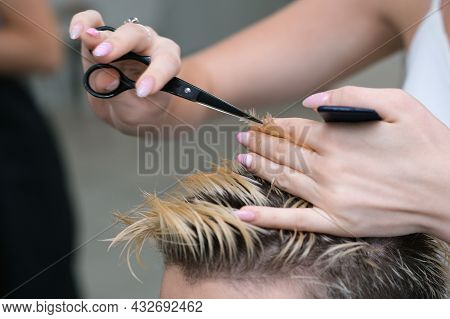 Hairdresser Cuts The Hair Of A Young Man With Blond Dyed Hair With Scissors In A Beauty Salon. Profe