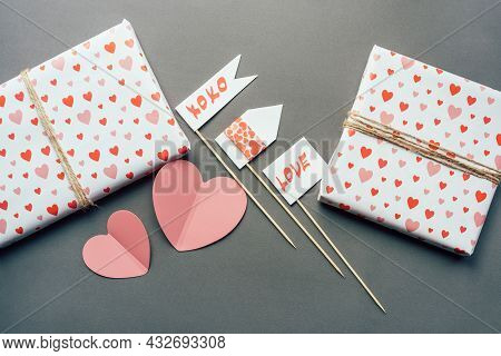 On The Gray Surface There Are Gift Boxes Wrapped In Textured Paper And Props With A Love Message. Fe