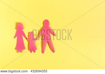 Cardboard Figures Of Two Adults And A Child On A Yellow Background. The Concept Of Family Relations