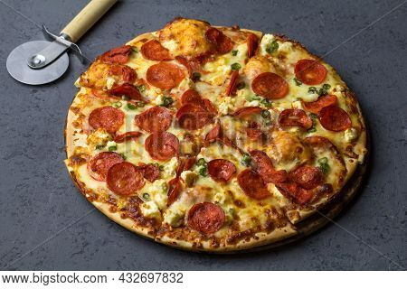 Tasty Pepperoni Pizza Made With Salami, Feta, Chile Peppers  On Black Concrete Background. Top View