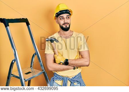Handsome man with beard wearing hardhat holding hammer by stairs smiling looking to the side and staring away thinking.