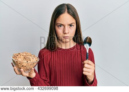 Beautiful brunette little girl eating healthy whole grain cereals holding spoon depressed and worry for distress, crying angry and afraid. sad expression.