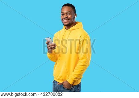 African American Guy Using Smartphone Wearing Earbuds Over Blue Background