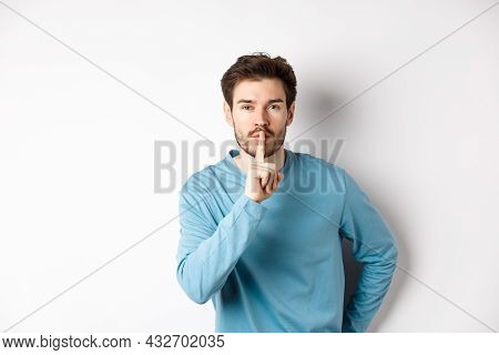 Attractive Bearded Man Asking To Keep Quiet, Showing Taboo Hush Gesture And Looking At Camera Calm,