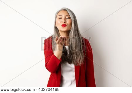 Elegant Asian Woman With Red Blazer And Lips, Blowing Air Kiss At Camera, Concept Of Valentines Day