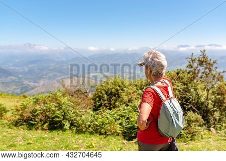 Senior Woman Hiker Contemplates The Landscape From The Top Of A Mountain