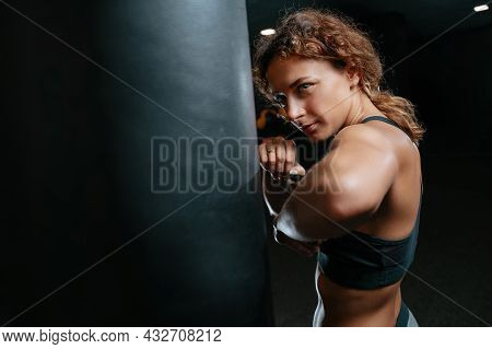 Muscular Woman In A Fighting Pose On A Black Background Hitting A Boxing Bag. Concept Of Fitness And