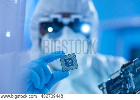 African-American scientist works in a modern scientific laboratory for the research and development of microelectronics and processors. Manufacturing worker uses computer technology and equipment.