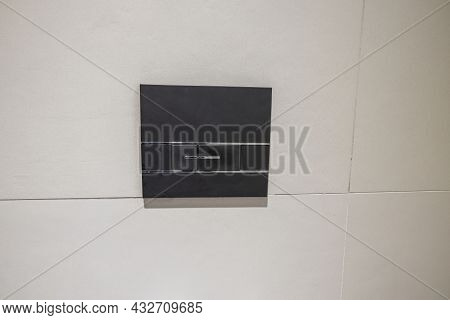 Close Up Macro View Of Black Flush Button On White Tiles Wall. Plumbing Concept.