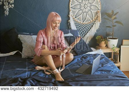 Joyful Lady With Pink Hair In Silk Gown Holds Phone Sitting Near Laptop On Large Bed