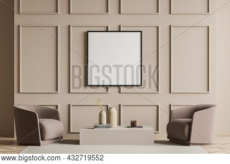 Empty Framed Canvas In A Beige Living Room Interior With Two Brown Armchairs, Wall Moulding, A Coffe