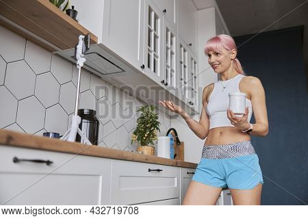 Fitness Trainer Holds Jar Of Dietary Supplement Shooting New Video In Kitchen