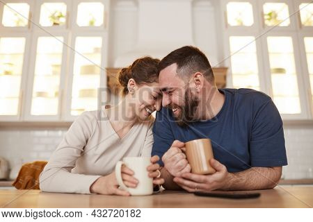Happy Affectionate Young Caucasian Couple Leaning On Kitchen Table And Laughing While Drinking Coffe