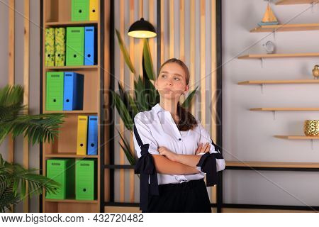 Young Beautiful Girl In Office Style Looks At The Camera. A Teenager In School Clothes In The Office