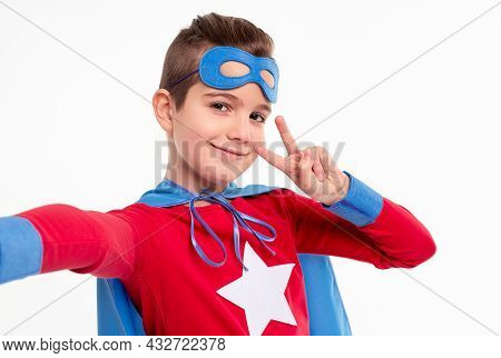 Positive Preteen Boy In Superhero Outfit And Mask Looking At Camera And Taking Selfie While Showing
