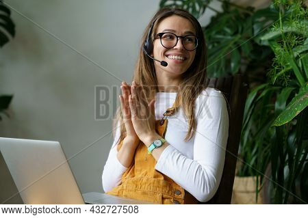 Young Woman Small Business Owner In Headset Talk With Client Or Partner Using Laptop Computer And Vi