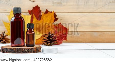 Essential Oil Bottle For Aromatherapy. Autumn Skin Care Concept. Cosmetic Serum On A Wooden Pedestal