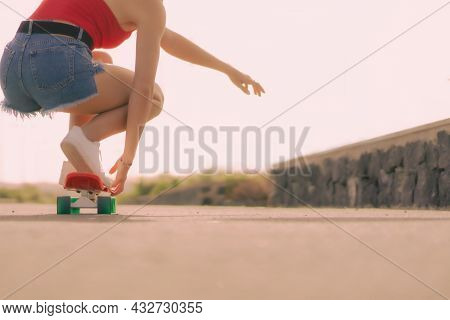 Closeup Of Young Woman On Skateboard In The Skate Park. Sport And Lifestyle Concept. Focus On Foot A