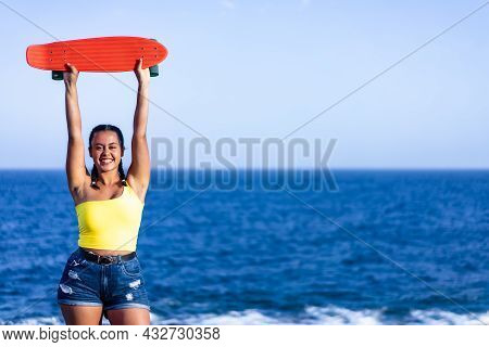 Young Woman Holding Her Skateboard On A Blue Sea Background. Copy Space. Lifestyle And Sport Concept