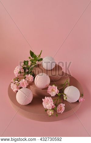Bath Bombs With Rose Extract.pink Bath Bombs And Rose Flowers On Burgundy Pedestal On A Pink Backgro
