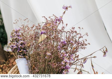 Violet Dried Caspia And Dried Statice Flowers Bouquet In Vintage Style. Garden Blur Background. Purp