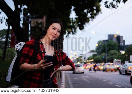 Young Asian Woman Holding Smart Phone And Waiting For Taxi On The Street.