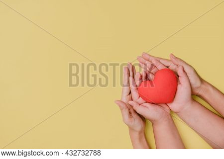 Mother And Son Hand Holding Red Heart On Yellow Background, Heart Health Insurance, Charity Voluntee
