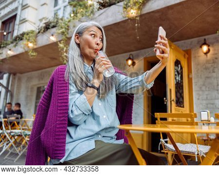 Funny Senior Asian Woman Drinks Water Through Straw Taking Selfie At Cafe Table Outdoors Low Angle V