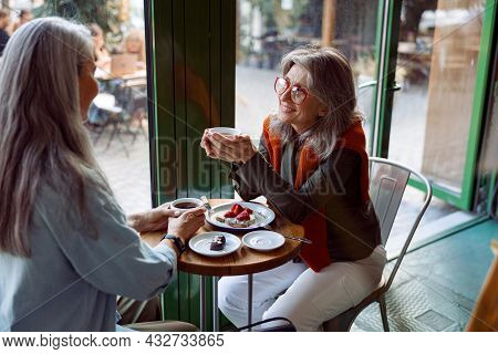 Positive Mature Woman And Companion With Grey Hair Enjoy Drinks At Table In Cozy Cafe