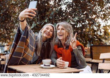 Joyful Senior Women Take Selfie With Smartphone Sitting At Small Table In Street Cafe