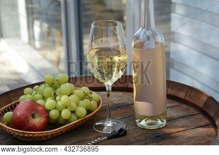 A Glass Of White Wine With Grapes On A Barrel. White Wine Riesling, From White Grapes