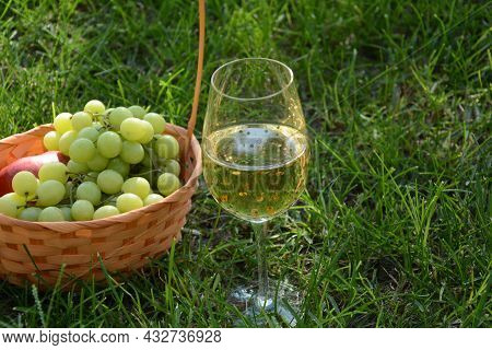 A Glass Of White Wine With Grapes On Green Grass. White Wine Riesling, From White Grapes