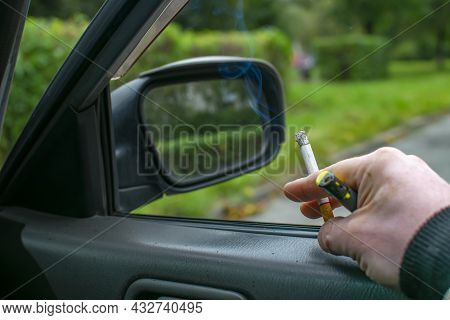A Smoking Cigarette With A Filter In The Hand Of The Driver Who Is Sitting Inside The Car, Waiting F