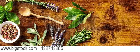 Culinary Herbs Panorama With Bay Leaf And A Place For Text, Shot From The Top On A Rustic Wooden Bac