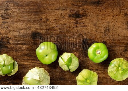 Tomatillos, Green Tomatoes, Top Shot With Copy Space. Mexican Food Ingredient On A Dark Rustic Woode