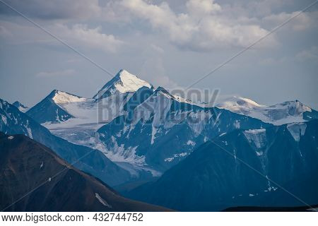 Awesome Mountains Landscape With Big Snowy Mountain Pinnacle In Blue White Colors Under Cloudy Sky.