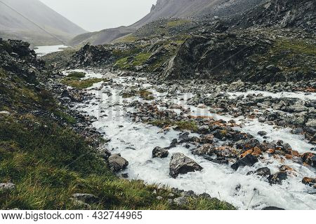 Atmospheric Landscape With Mountain Lake And Mountain Creek Among Moraines In Rainy Weather. Bleak O