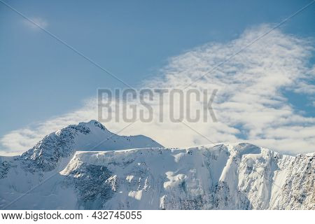 Minimalist Alpine Landscape With High Snow-covered Mountain With Snowy Peaked Top Under Cirrus Cloud