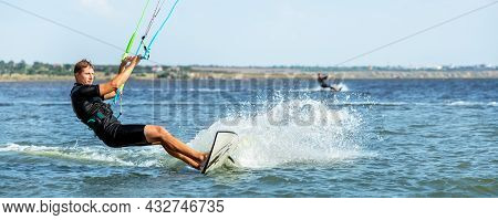 Young Adult Caucasian Fit Male Person Enjoy Riding Kite Surf Board In Sun Uv Protection Suit On Brig