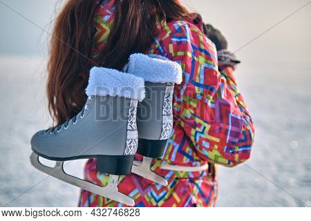 A Woman In A Ski Suit Holds Skates On Her Shoulder, After Skiing On A Frozen Lake, Closeup