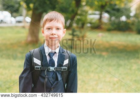 A Schoolboy In A School Uniform And A Backpack Stands On The Street. Boy In School Uniform. Back To