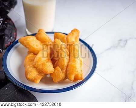 Close-up Of Deep-fried Dough Sticks Or Chinese Doughnut Sticks On White Plate And A Glass Of Soybean