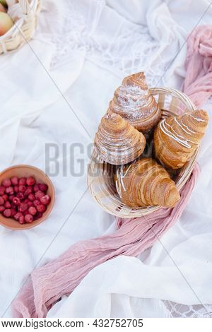Red Berries On Plate Near Croissants And Flowers On White Blanket, Picnic