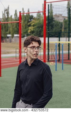 Portrait Of A Young Man In Front Of The Running Tracks At A Sports Stadium. A Man Wearing Glasses An
