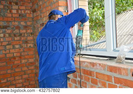 Plastic Window Installation In A New Brick House. A Professional Window Installer Is Installing A Up