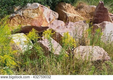 Large Blocks Of Red Granite With Torn Edges With Marks Of Imploding Works Lie Among Flowering Grass