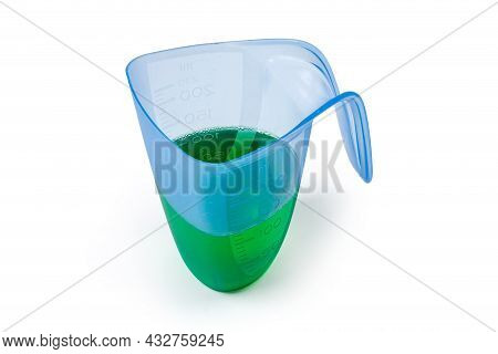 Green Liquid Laundry Detergent Poured In Blue Transparent Plastic Measuring Cup On A White Backgroun