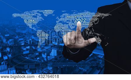 Businessman Pressing 2022 Start Up Business Icon With Global Words World Map Over Modern City Tower,
