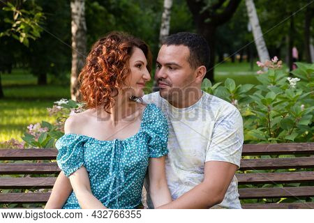 Loving Couple On A Park Bench Look At Each Other With Tenderness. Man And A Curly Woman In A Blue Dr